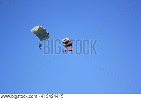 Parasailing, Two Paratroopers Flying Against A Blue Sky.