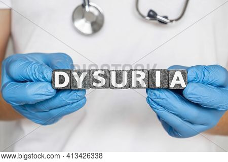 Dysuria - Word From Stone Blocks With Letters Holding By A Doctor's Hands In Medical Protective Glov