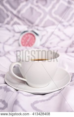 Close Up Of A Coffee Cup Placed On Modern Bed Sheets With An Alarm Clock In The Background. Morning