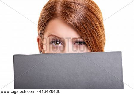 Close Up Portrait Of A Young Woman Hiding Her Face Behind A Book, With One Brow Up Looking At The Ca