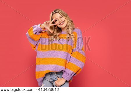 Pretty Blonde Woman In Fashionable Sweater Posing On Studio Colorful Background. Fashionista Lady Sm