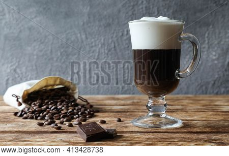 Irish Coffee In A Beautiful Glass With Handle With A Bar Of Chocolate
