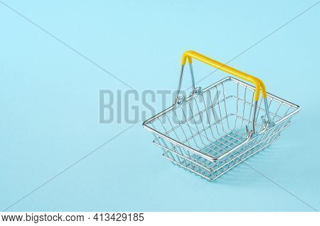 Empty Metal Wire Shopping Basket With Yellow Handles Isolated On Blue Background. Consumerism Concep