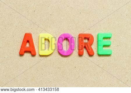 Color Alphabet Letter With Word Adore On Wood Background