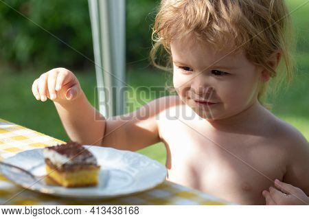 Baby Eating Cake. Cute Child Boy Kid Eats Delicious Dessert Sunny Summer Day On Natural Background