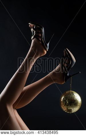Disco Party Event. Woman Legs With Gold Disco Ball. Celebrate Concept. Gold Disco Ball On High Heels