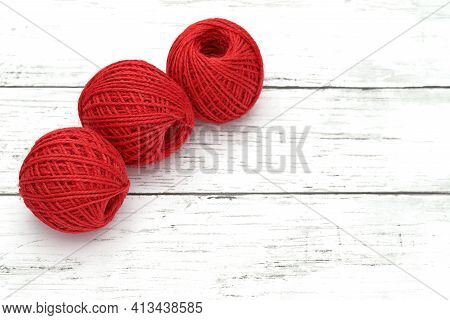 Ball Of Red Threads On White Wooden Table