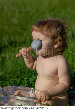 Spoon Feeding Baby. Funny Child Face. Feeding Baby With Big Spoon Outdoor On Green Grass. Springtime