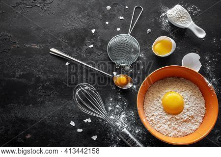Flour, Chicken Eggs And Baking Dish On A Black Background With Place For Text