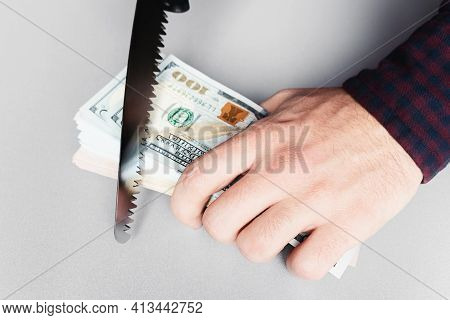 Holding Money And Saws With A Saw Close Up Concept Corruption, Budget Theft