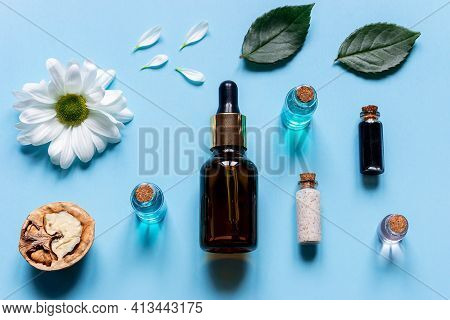 Perfume Cosmetics From Natural Ingredients On A Blue Background Flowers And Walnut Close-up