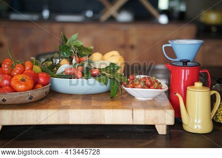 Tomatoes, Lemon, Indian Ivy-rue And Tea Pot In Kitchen