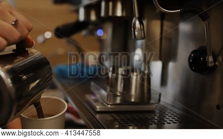 The Barista Prepares Coffee For The Guest. The Girl Pours Ready-made Coffee Into A Glass On The Back