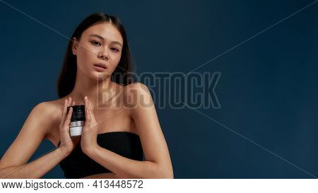 Asian Girl Looking At The Camera While Holding Cosmetics In Her Hands. Youth And Beauty In A Beautif