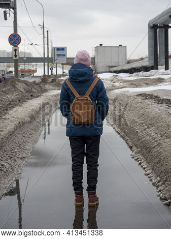 A Woman In A Blue Jacket With A Backpack Walks Through The Spring City. Puddles On The Road, Slush,