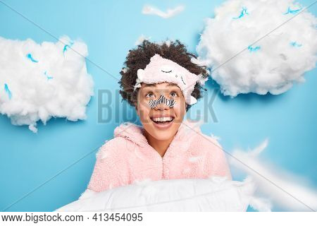 Cheerful Curly Haired Young Woman Wears Applicator Mask On Nose Dressed In Nightwear Looks Gladfully