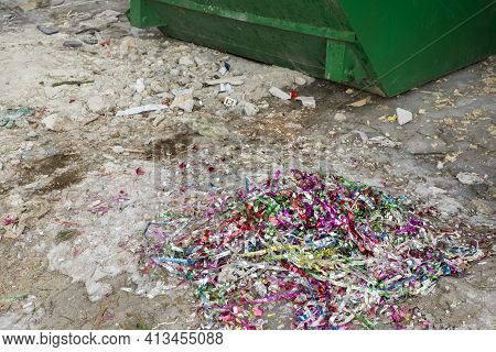 Tinsel Scattered On The Ground Next To A Rubbish Container, Outdoor Shot