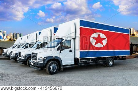North Korea Flag On The Back Of Five New White Trucks Against The Backdrop Of The River And The City
