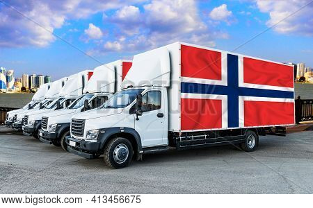 Norway Flag On The Back Of Five New White Trucks Against The Backdrop Of The River And The City. Tru