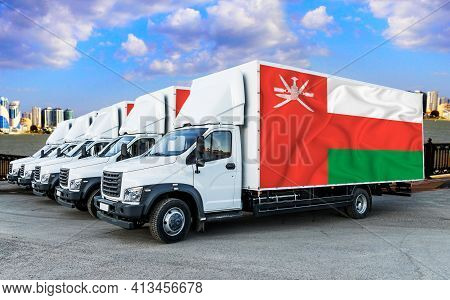 Oman Flag On The Back Of Five New White Trucks Against The Backdrop Of The River And The City. Truck