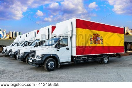 Spain Flag On The Back Of Five New White Trucks Against The Backdrop Of The River And The City. Truc