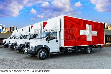 Switzerland Flag On The Back Of Five New White Trucks Against The Backdrop Of The River And The City
