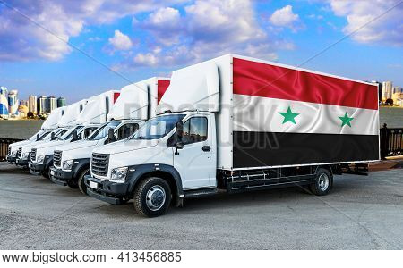 Syria Flag On The Back Of Five New White Trucks Against The Backdrop Of The River And The City. Truc