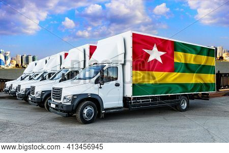Togo Flag On The Back Of Five New White Trucks Against The Backdrop Of The River And The City. Truck