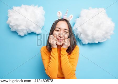 Nice Looking Young Asian Woman Keeps Hands Under Chin Smiles Gently Has Dark Hair Wears Casual Orang