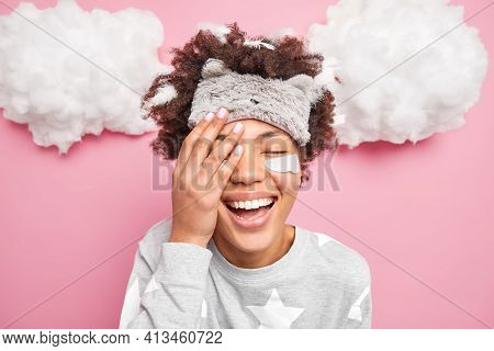 Glad Positive African American Girl Covers Face Closes Eyes And Smiles Gladfully Enjoys Good Morning