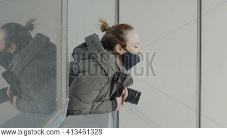 Female Photographer Looks Out Of Window With Camera. Action. Masked Paparazzi Woman With Camera Look