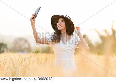 Happy Young Beautiful Woman Wearing Black Hat And White Dress Taking Selfie While Walking In The Gol