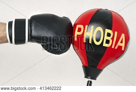 Fight The Phobia Concept With A Strong Man's Hand In A Boxing Glove Hits The Punching Bag With Text