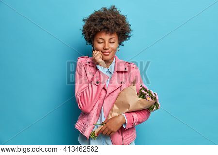 Pleased Young Curly African American Woman Closes Eyes Feels Pleasure Holds Flowers Wrapped In Paper