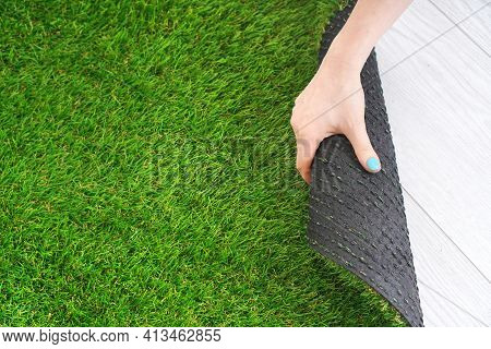 Woman's Hand Unwinds A Roll Of Artificial Turf. Copy Space.