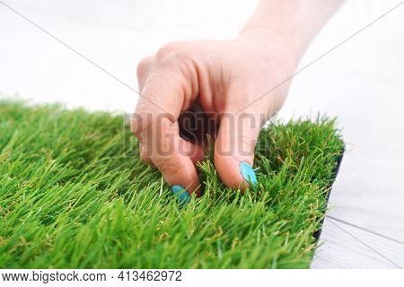 Woman's Hand Touches The Artificial Turf Roll