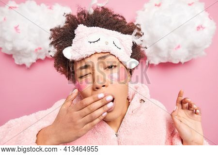 Headshot Of Curly Haired Young African American Woman Covers Mouth With Hand Has Sleepy Expression W