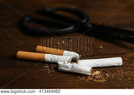 Cut Cigarettes And Scissors On Wooden Table, Closeup. Quitting Smoking Concept