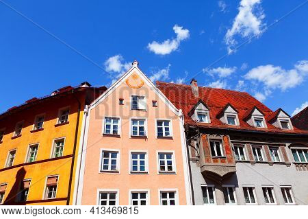 Colorful Tenement Houses With Attics . Facade With Sundial . European Residential District