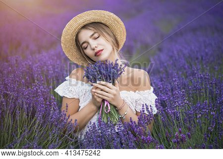 Young Blond Woman In Lavender Field. Happy Carefree Female In A White Dress And Straw Hat Enjoying S