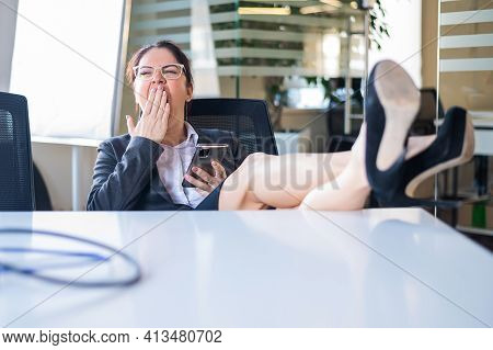 Business Woman Folded Her Legs On The Desk And Yawns. Boredom At Work.
