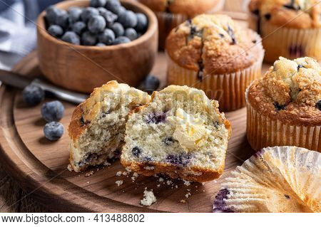 Blueberry Muffin Cut In Half With Butter And Berries And Muffins In Background On A Wooden Platter