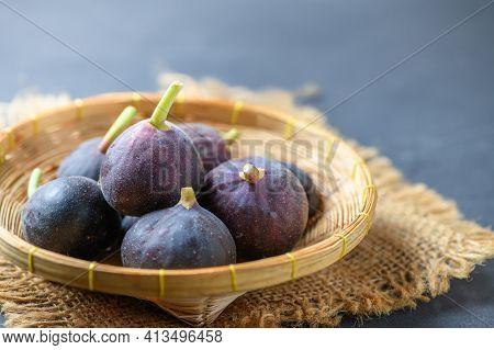 Fresh Ripe Figs In Bamboo Basket On Dark Table. Healthy Mediterranean Fig Fruit. Fresh Figs On Black