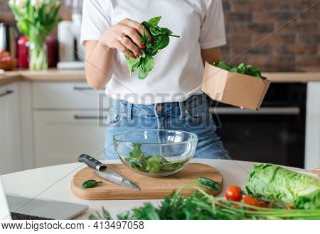 Close Up Woman In White T-shirt Cooking Salad With Motion Effect At Home Kitchen. Process Of Cooking