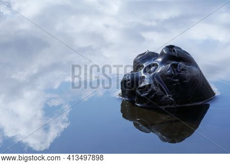 Black Plastic Bottle Floating In River At The Water Surface, Reflection Of Sky And Clouds In Water,