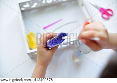 A Girl Girl Sprinkles Paraffin With A Spoon Makes Makes A Candle From Small Paraffin Granules. Kids