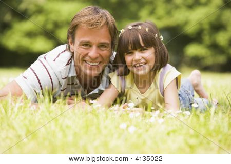 Portrait of daughter putting daisy chain on mans head poster