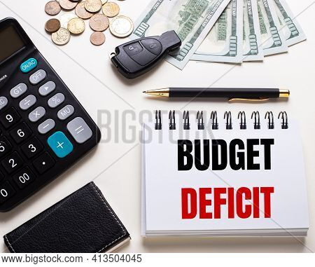 On A White Table Is A Calculator, Car Key, Cash, A Pen And A Notebook With The Inscription Budget De