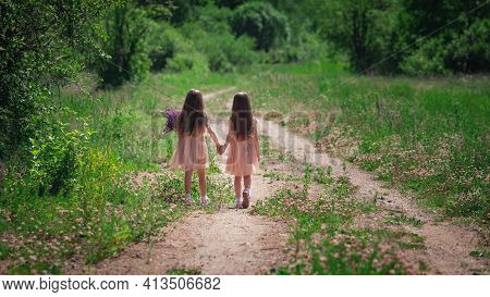 Backwards View Of Little Identical Twin Sisters With Long Hair Walking Together Holding Hands At Roa