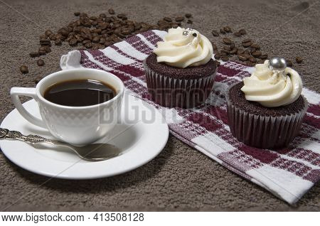 Two Cupcakes On Fabric Background, White Coffee Cup, Homemade Cake With Cream And Roasted Coffee Bea